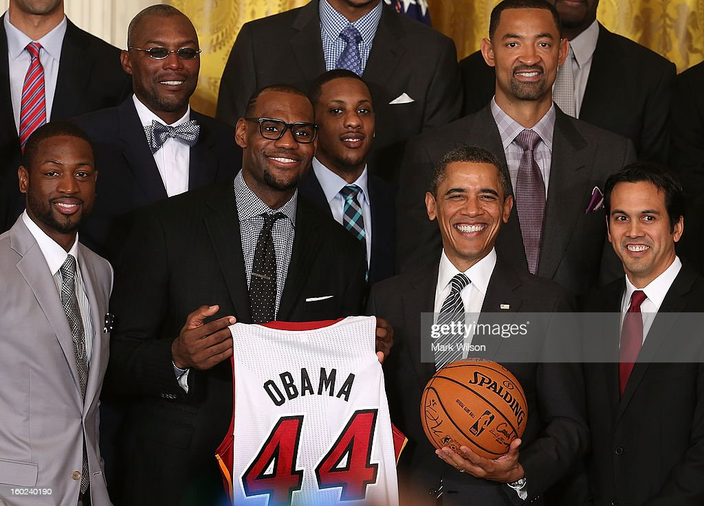U.S. President Barack Obama (2nd-R) stands with Miami Heat players, including Dwyane Wade (L), LeBron James (2nd-L), Mario Chalmers (C) and Head coach Erik Spoelstra, (R) during an event to honor the NBA champion Miami Heat in the East Room at the White House on January 28, 2013 in Washington, DC. President Barack Obama congratulated the 2012 NBA champions for claiming their third NBA Championship by beating the Boston Celtics.