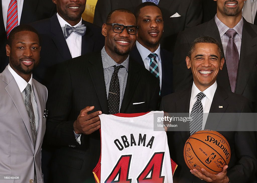U.S. President Barack Obama (R) stands with Miami Heat players, including Dwyane Wade (L), LeBron James (2nd-L), Mario Chalmers (2R) during an event to honor the NBA champion Miami Heat in the East Room at the White House on January 28, 2013 in Washington, DC. President Barack Obama congratulated the 2012 NBA champions for claiming their third NBA Championship by beating the Boston Celtics.