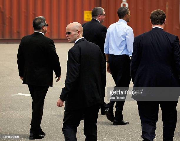 S President Barack Obama surrounded by Secret Service agents walks away after a visit to the Port of Tampa on April 13 2012 in Tampa Florida The...