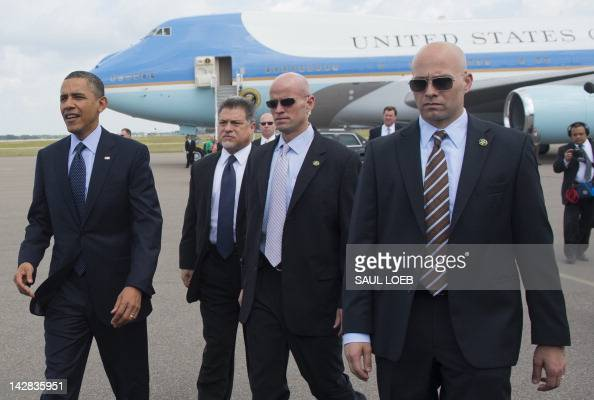US President Barack Obama surrounded by US Secret Service agents walks to greet guests upon arrival on Air Force One at Tampa International Airport...