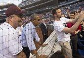 US President Barack Obama takes a photo with a fan alongside Representative Dan Kildee Democrat of Michigan during the annual Congressional Baseball...