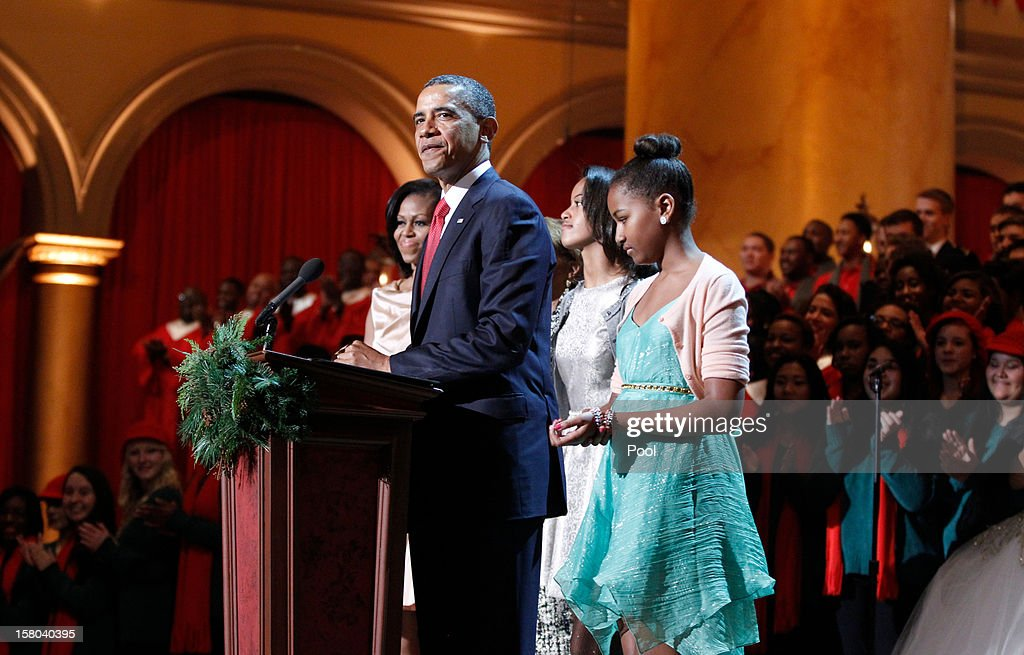 U.S. President Barack Obama (C) takes part in the 'Christmas in Washington' concert with first lady Michelle Obama (L) and daughters Malia and Sasha Obama (R) at the National Building Museum on December 9, 2012 in Washington, D.C. The concert benefits the National Childrens Medical Center and is hosted by comedian Conan O'Brien.