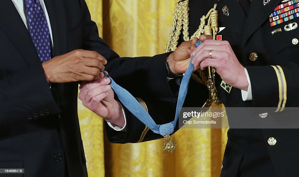 U.S. President <a gi-track='captionPersonalityLinkClicked' href=/galleries/search?phrase=Barack+Obama&family=editorial&specificpeople=203260 ng-click='$event.stopPropagation()'>Barack Obama</a> (L) takes the Medal of Honor from his military aide before awarding it to former U.S. Army Captain William Swenson during a ceremony in the East Room of the White House October 15, 2013 in Washington, DC. Honored for his actions in the 2009 Battle of Ganjgal Valley in the Kunar Province of Afghanistan, Swenson is the sixth living veteran of the Iraq and Afghanistan wars to receive the Medal of Honor, awarded to a person who 'distinguished himself conspicuously by gallantry and intrepidity at the risk of his life above and beyond the call of duty.'