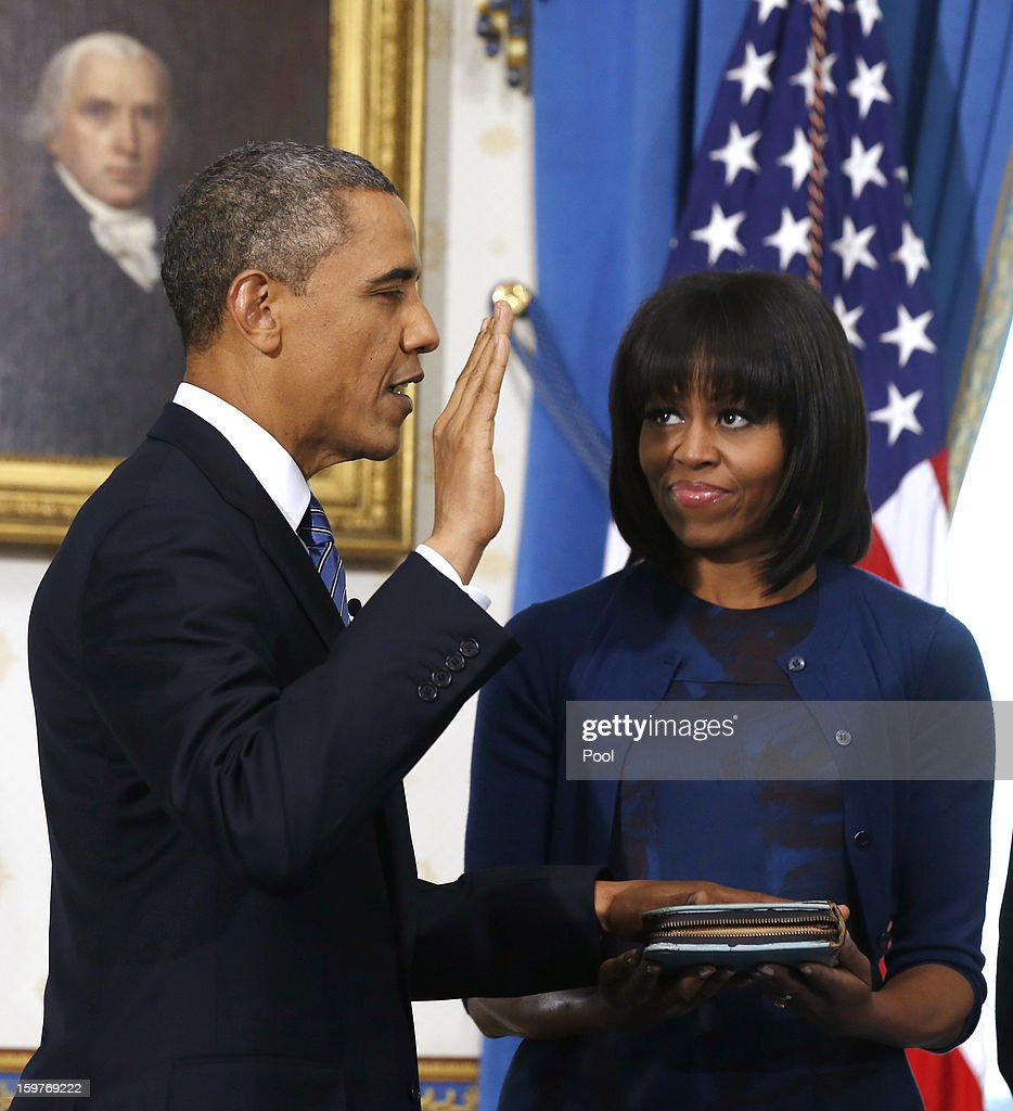 President <a gi-track='captionPersonalityLinkClicked' href=/galleries/search?phrase=Barack+Obama&family=editorial&specificpeople=203260 ng-click='$event.stopPropagation()'>Barack Obama</a> (L) takes the oath of office as first lady Michelle Obama holds the bible in the Blue Room of the White House January 20, 2013 in Washington, DC. Obama and U.S. Vice President Joe Biden were officially sworn in a day before the ceremonial inaugural swearing-in.