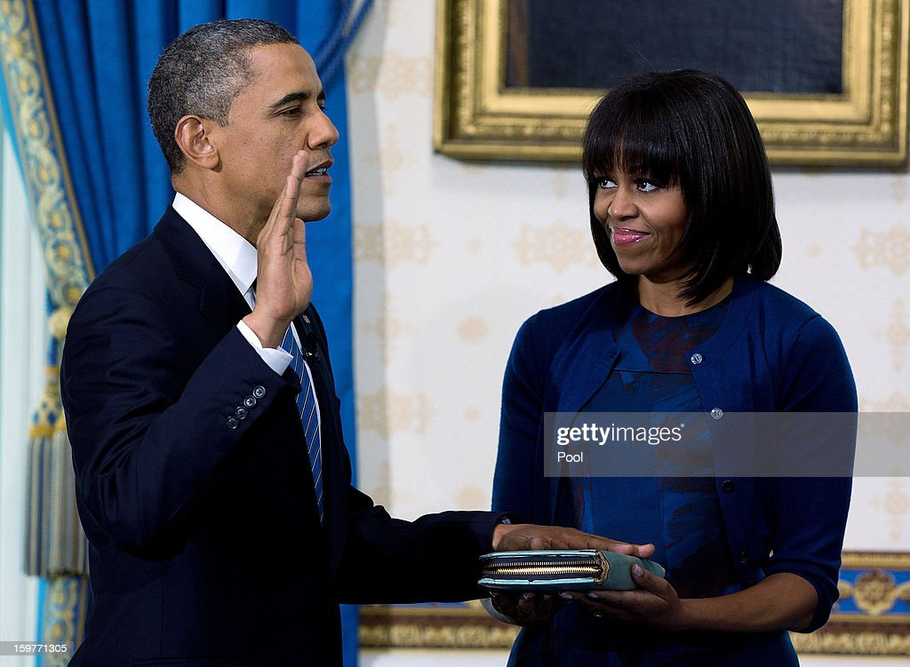 President Barack Obama (L) takes the oath of office as first lady Michelle Obama holds the bible in the Blue Room of the White House January 20, 2013 in Washington, DC. Obama and U.S. Vice President Joe Biden were officially sworn in a day before the ceremonial inaugural swearing-in.