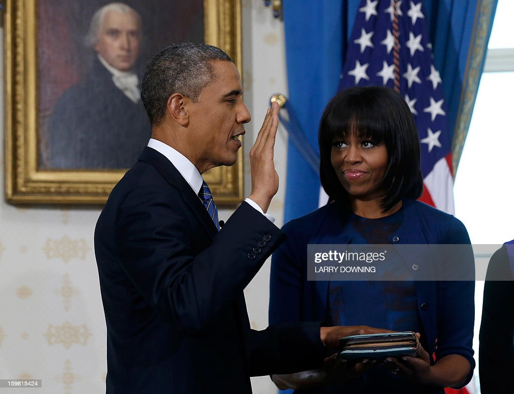 US President Barack Obama (L) takes the oath of office as first lady Michelle Obama holds the bible in the Blue Room of the White House in Washington ON January 20, 2013. AFP PHOTO/Larry Downing/Pool