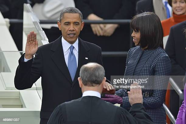 President Barack Obama takes the oath of office from Supreme Court Chief Justice John Roberts as First Lady Michelle Obama holds the two Bibles...