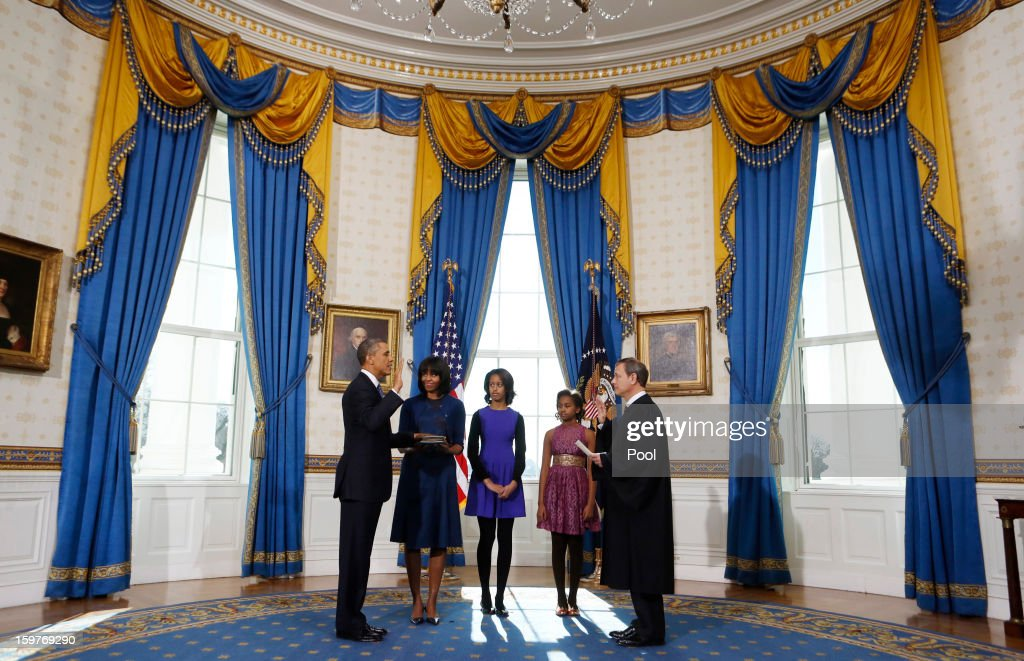 President <a gi-track='captionPersonalityLinkClicked' href=/galleries/search?phrase=Barack+Obama&family=editorial&specificpeople=203260 ng-click='$event.stopPropagation()'>Barack Obama</a> (L) takes the oath of office from U.S. Supreme Court Chief Justice John Roberts (R) as first lady <a gi-track='captionPersonalityLinkClicked' href=/galleries/search?phrase=Michelle+Obama&family=editorial&specificpeople=2528864 ng-click='$event.stopPropagation()'>Michelle Obama</a> (2nd L) holds the bible and daughter Malia (C) and Sasha looks on in the Blue Room of the White House January 20, 2013 in Washington, DC. Obama and U.S. Vice President Joe Biden were officially sworn in a day before the ceremonial inaugural swearing-in.