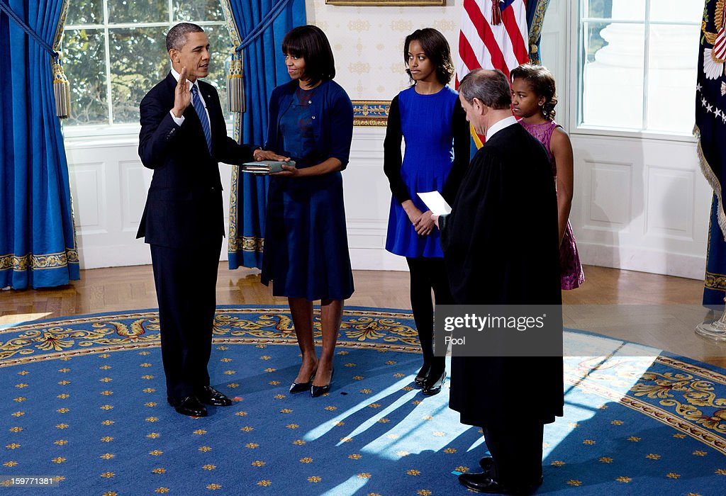 President <a gi-track='captionPersonalityLinkClicked' href=/galleries/search?phrase=Barack+Obama&family=editorial&specificpeople=203260 ng-click='$event.stopPropagation()'>Barack Obama</a> (L) takes the oath of office from U.S. Supreme Court Chief Justice <a gi-track='captionPersonalityLinkClicked' href=/galleries/search?phrase=John+Roberts+-+17th+Chief+Justice+of+the+United+States&family=editorial&specificpeople=2220360 ng-click='$event.stopPropagation()'>John Roberts</a> (R) as first lady <a gi-track='captionPersonalityLinkClicked' href=/galleries/search?phrase=Michelle+Obama&family=editorial&specificpeople=2528864 ng-click='$event.stopPropagation()'>Michelle Obama</a> (2nd L) holds the bible and daughter Malia (C) and Sasha looks on in the Blue Room of the White House January 20, 2013 in Washington, DC. Obama and U.S. Vice President Joe Biden were officially sworn in a day before the ceremonial inaugural swearing-in.