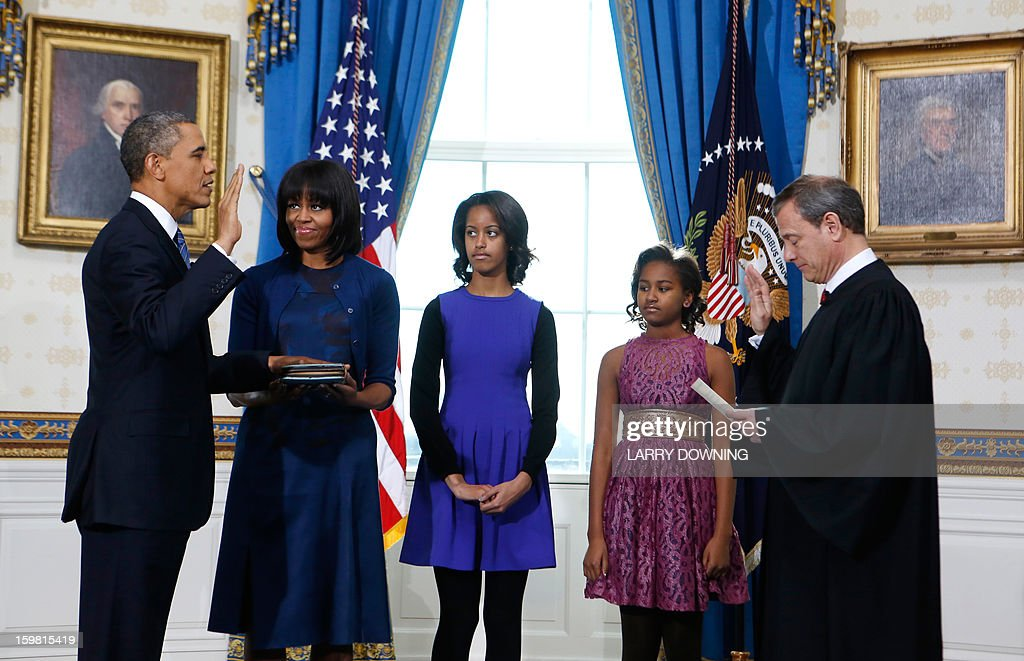 US President Barack Obama (L) takes the oath of office from US Supreme Court Chief Justice John Roberts as first lady Michelle Obama holds the bible and their daughters Malia (C) and Sasha (2nd R) look on in the Blue Room of the White House in Washington on January 20, 2013. AFP PHOTO/Larry Downing/Pool