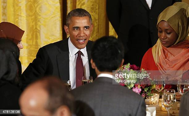 US President Barack Obama talks to guests during an Iftar dinner celebrating Ramadan in the State Dining Room at the White House in Washington DC on...