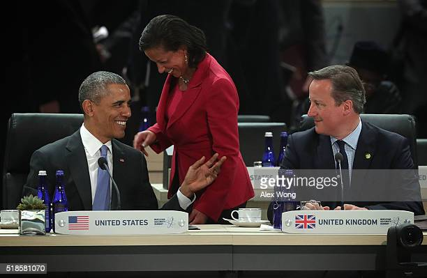 US President Barack Obama talks to National Security Adviser Susan Rice as Prime Minister of the United Kingdom David Cameron looks on during a...