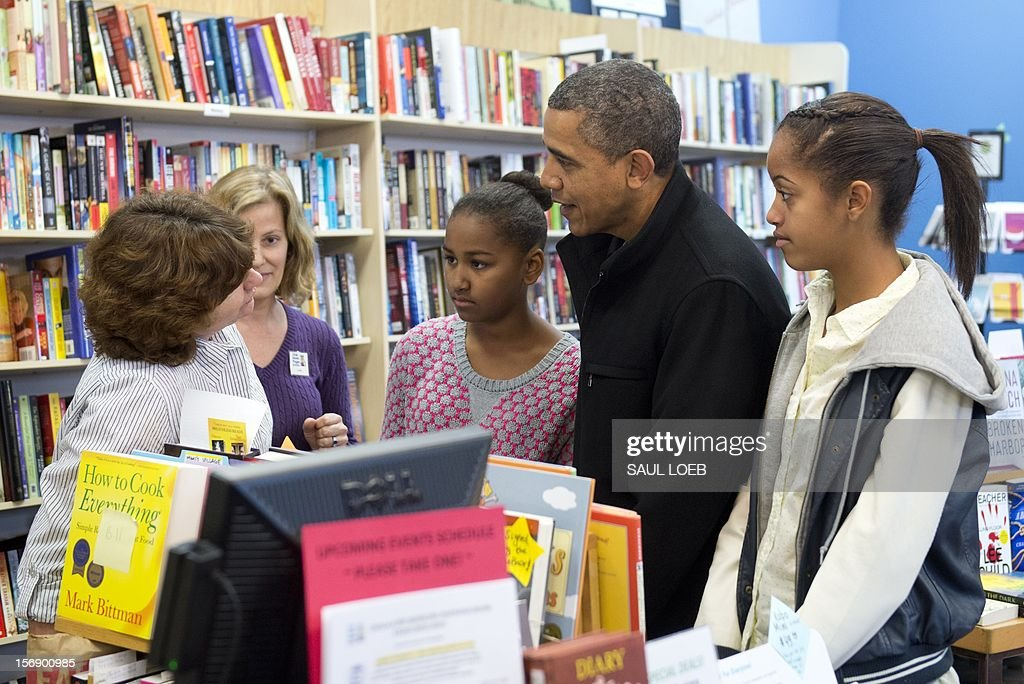 US President Barack Obama talks with a shopkeeper alongside his daughters Sasha (C) and Malia (R) during a shopping trip to One More Page Books on Small Business Saturday, which promotes shopping at local small businesses, in the Falls Church neighborhood of Arlington, Virginia, on November 24, 2012. AFP PHOTO / Saul LOEB