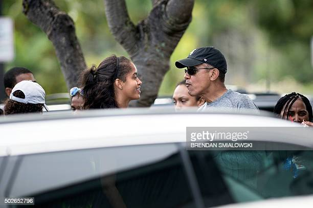 US President Barack Obama talks with his daughter Malia Obama while stopping for shaved ice at Island Snow after a visit to the beach December 27...