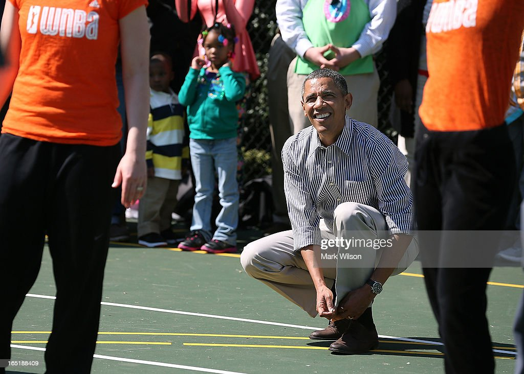 U.S. President <a gi-track='captionPersonalityLinkClicked' href=/galleries/search?phrase=Barack+Obama&family=editorial&specificpeople=203260 ng-click='$event.stopPropagation()'>Barack Obama</a> ties his shoe while playing basketball with children during the annual Easter Egg Roll on the White House tennis court April 1, 2013 in Washington, DC. Thousands of people are expected to attend the 134-year-old tradition of rolling colored eggs down the White House lawn that was started by President Rutherford B. Hayes in 1878.