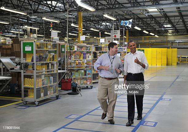 US President Barack Obama tours an Amazon fulfillment center with Amazon's Vice President for Worldwide Operations Dave Clark on July 30 2013 in...