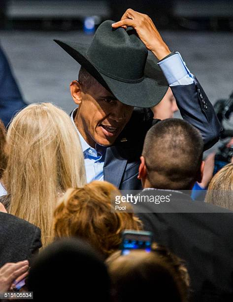 S President Barack Obama tries on a cowboy hat from a member of the crowd after speaking at a private Democratic National Committee event at Gilley's...