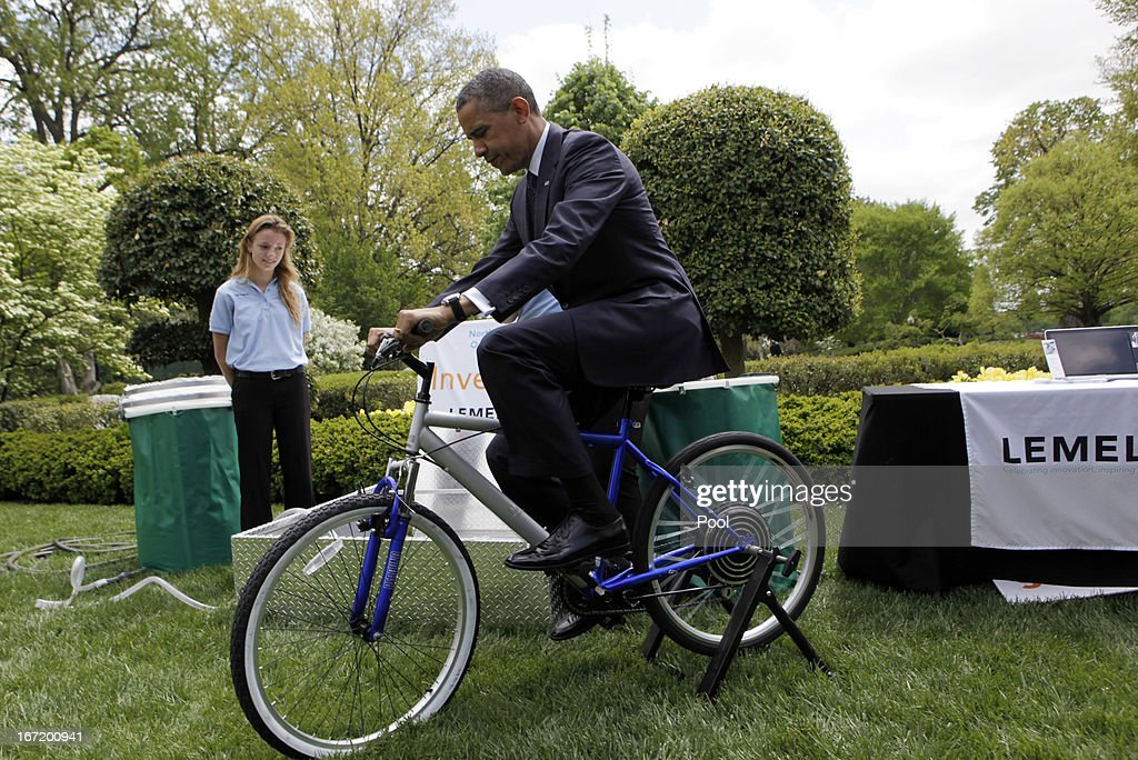 U.S. President Barack Obama tries the bicycle-powered emergency water-sanitation station, created by high schoolers Payton Karr and Kiona Elliot from Oakland Park, Florida in the East Garden of the White House, during the White House Science Fair April 22, 2013 in Washington, DC. The White House Science Fair celebrates the student winners of a broad range of science, technology, engineering and math (STEM) competitions from across the country. The first White House Science Fair was held in late 2010.