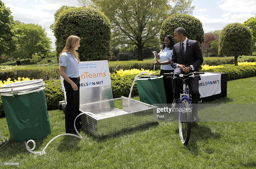 U.S. President <a gi-track='captionPersonalityLinkClicked' href=/galleries/search?phrase=Barack+Obama&family=editorial&specificpeople=203260 ng-click='$event.stopPropagation()'>Barack Obama</a> tries the bicycle-powered emergency water-sanitation station, created and presented by high schoolers Payton Karr (L) and Kiona Elliot (R) from Oakland Park, Florida, in the East Garden of the White House, during the White House Science Fair April 22, 2013 in Washington, DC. The White House Science Fair celebrates the student winners of a broad range of science, technology, engineering and math (STEM) competitions from across the country. The first White House Science Fair was held in late 2010.