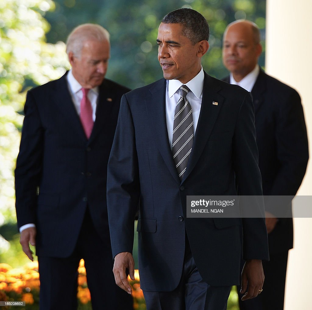 US President Barack Obama (C), US Vice President Joe Biden (L) and Jeh Johnson make their way through the Colonnade for a presss conference in the Rose Garden of the White House on October 18, 2013 in Washington, DC. Obama announced Johnson as his choice to be the next homeland Security secretary. AFP PHOTO/Mandel NGAN