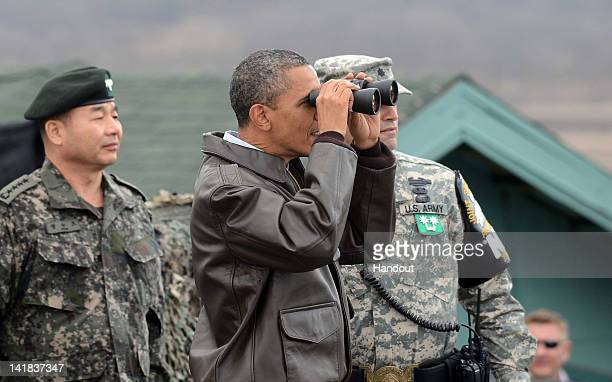 S President Barack Obama uses binoculars to look at North Korea from the Observation Post Ouellette in the Demilitarized Zone which separates the two...