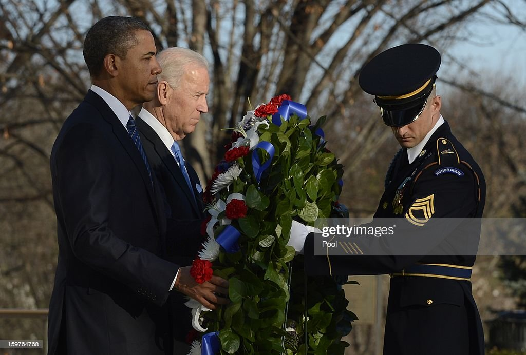 President Barack Obama, Vice President Joe Biden and Sergeant First Class Chad E. Stackpole participate in a wreath-laying ceremony at the Tomb of the Unknown Soldier January 20, 2013 in Arlington National Cemetery, Arlington, Virginia. Both Obama and Biden will be sworn in today for a second term in office.