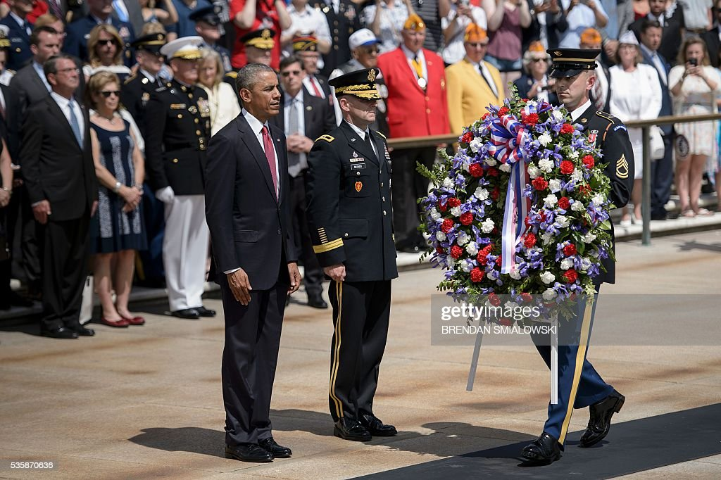 US President Barack Obama (L) waits with US Major General Bradley A. Becker (C), Commander of the Military District of Washington, to place a wreath at the Tomb of the Unknowns to honor Memorial Day at Arlington National Cemetery May 30, 2016 in Arlington, Virginia. / AFP / Brendan Smialowski