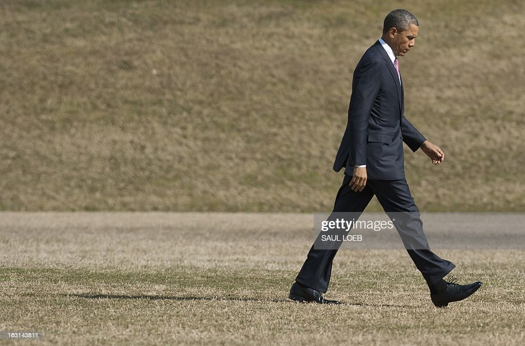 US President Barack Obama walks across a field after arriving on Marine One at Walter Reed National Military Medical Center in Bethesda, Maryland, March 5, 2013. Obama is visiting with wounded warriors who are being treated at the hospital and their families. AFP PHOTO / Saul LOEB
