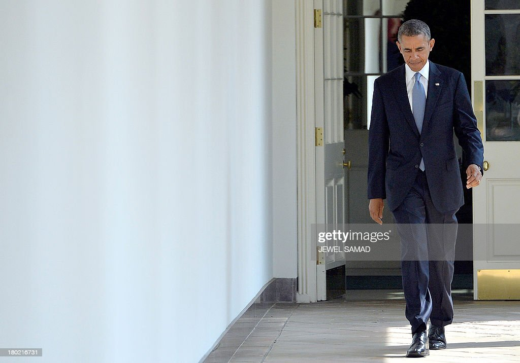 US President Barack Obama walks along the colonnade at the White House to the Oval Office on September 10, 2013 in Washington, DC. President Obama has agreed with his French and British counterparts to probe Russia's plan to defuse the Syria chemical weapons crisis at the United Nations on Tuesday, a US official said. The discussion will test the viability of the plan with a view to enshrining commitments in a Security Council resolution, the official said. The strategy was agreed in separate phone calls between Obama and French President Francois Hollande and British Prime Minister David Cameron on Tuesday, the official said. AFP PHOTO/Jewel Samad
