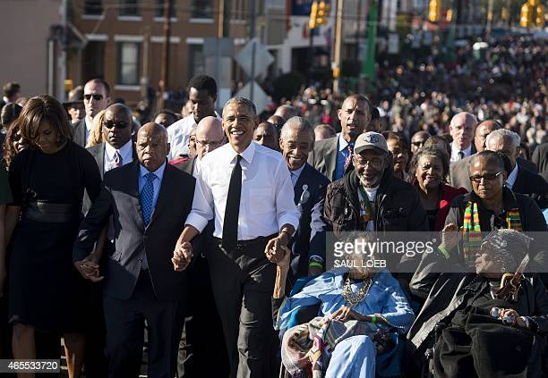 US President Barack Obama walks alongside Amelia Boynton Robinson one of the original marchers First Lady Michelle Obama and US Representative John...