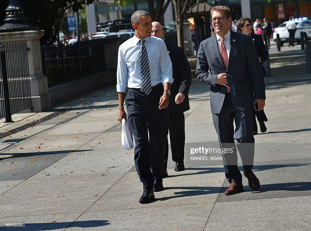 US President Barack Obama walks back to the White House with Press Secretary Jay Carney (R) after picking up lunch at Taylor Gourmet Deli on Pennsylvania Ave in Washington, DC on October 4, 2013. Obama walked over to the deli with US Vice President Joe Biden and ordered sandwiches to go. AFP PHOTO/Mandel NGAN