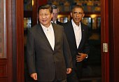 US President Barack Obama walks behind China's President Xi Jinping as they enter a room before a meeting after participating in the Asia Pacific...