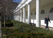 US President Barack Obama walks down the West Wing Colonnade at the White House in Washington DC February 12 2013 Obama will deliver his first State...