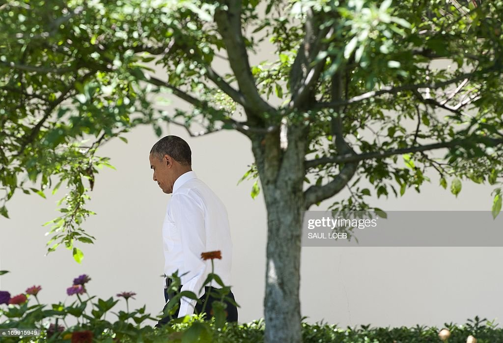 US President Barack Obama walks down the West Wing Colonnade prior to departing on Marine One from the South Lawn of the White House in Washington, DC, June 4, 2013, as he travels to Walter Reed National Military Medical Center to visit with wounded members of the military. AFP PHOTO / Saul LOEB
