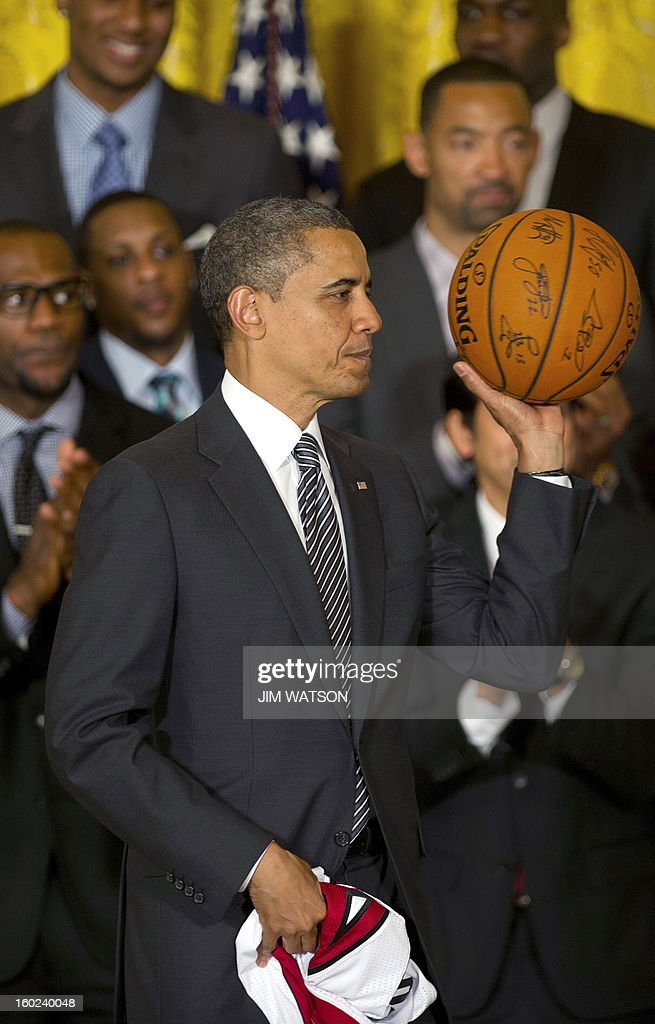 US President Barack Obama walks off with a basketball and jersey after welcoming the NBA Champion Miami Heat to the White House to honor the team and their 2012 NBA Championship victory at the White House in Washington, DC, January 28, 2013. AFP PHOTO/Jim WATSON
