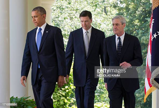 US President Barack Obama walks out of the Oval Office with outgoing Federal Bureau of Investigations director Robert Mueller and Obama's nominee to...