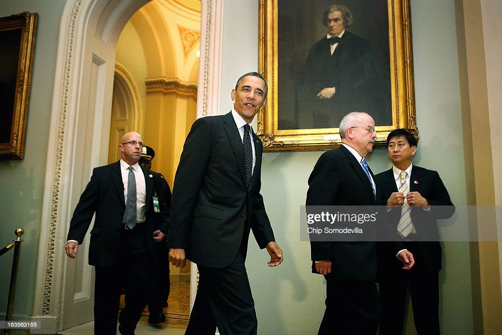 U.S. President Barack Obama walks past a portrait of former Vice President John C. Calhoun as he arrives for a meeting with members of the Senate Democatic Caucus in the Mansfield Room at the U.S. Capitol March 12, 2013 in Washington, DC. With tax reform, spending cuts, gun control and immigration on the agenda, Obama will be holding four meetings over three days this week with Republican and Democratic members of Congress at the U.S. Capitol.