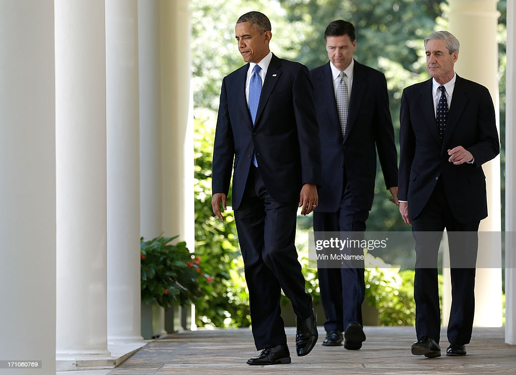 U.S. President Barack Obama (L) walks to a news conference to announce his nomination of James Comey (C) to become FBI Director, with outgoing director Robert Mueller in the Rose Garden at the White House June 21, 2013 in Washington, DC. Comey, a former Justice Department official under President George W. Bush, would replace Mueller.