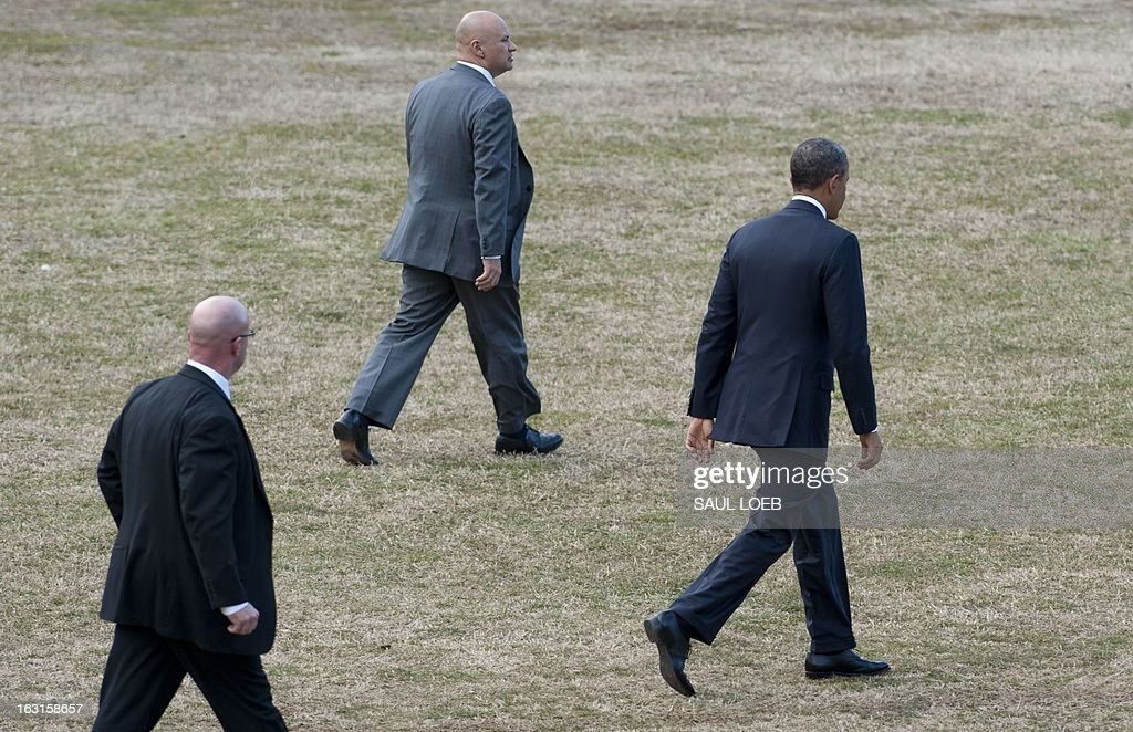 US President Barack Obama walks to Marine One surrounded by members of the US Secret Service as he departs Walter Reed National Military Medical Center in Bethesda, Maryland, March 5, 2013. Obama visited with Wounded Warriors who are being treated at the hospital and their families. AFP PHOTO / Saul LOEB