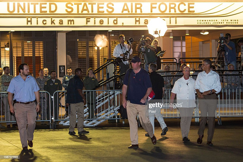 US President <a gi-track='captionPersonalityLinkClicked' href=/galleries/search?phrase=Barack+Obama&family=editorial&specificpeople=203260 ng-click='$event.stopPropagation()'>Barack Obama</a> walks with a Secret Service detail before boarding Air Force One at Joint Base Pearl Harbor-Hickam on December 26, 2012 in Honolulu, Hawaii. The president, who was spending a traditional Christmas holiday with his family in Hawaii, has been forced to cut his Christmas break short by the fiscal cliff crisis.
