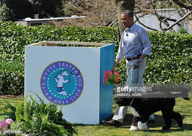 US President Barack Obama walks with Bo the family dog as he arrives to read a story to children attending the annual Easter Egg Roll on April 1 2013...