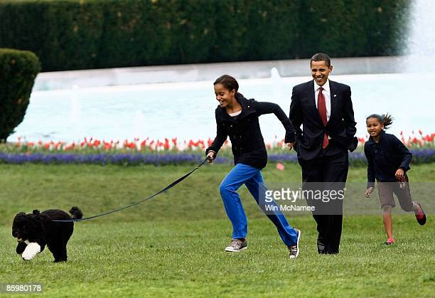 S President Barack Obama walks with daughters Malia and Sasha as they take their new Portuguese water dog Bo for a walk on the South Lawn of the...