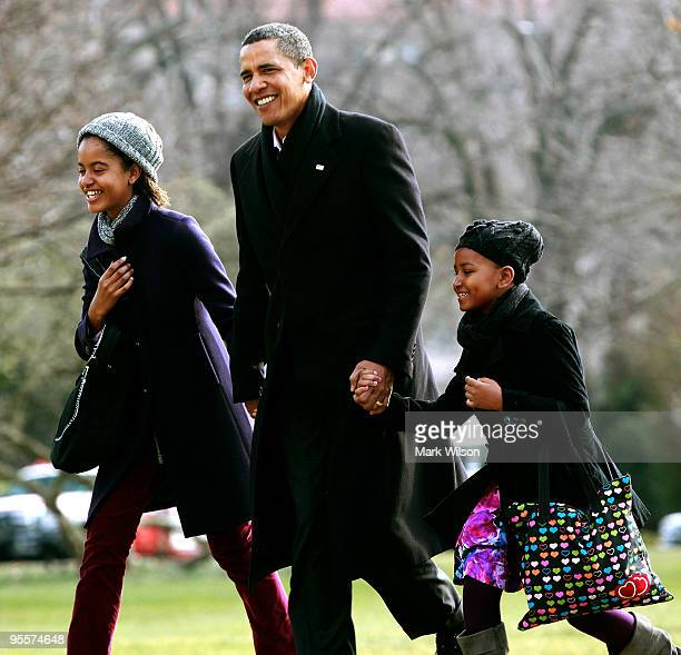 President Barack Obama walks with his daughters Malia and Sasha after they arrive on the South Lawn of the White House on January 4 2010 in...