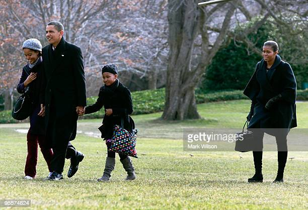 S President Barack Obama walks with his daughters Malia and Sasha and first lady Michelle Obama as they arrive on the South Lawn of the White House...