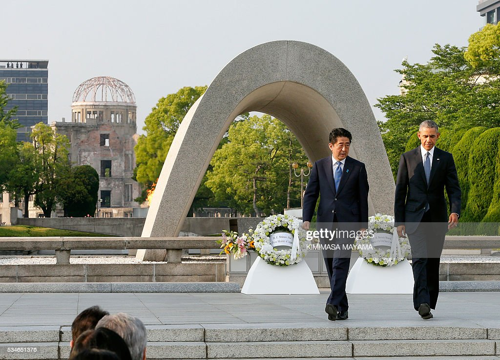 US President Barack Obama (R) walks with Japanese Prime Minister Shinzo Abe after laying wreaths in front of a cenotaph to offer a prayer for victims of the atomic bombing in 1945, at Hiroshima Peace Memorial Park in Hiroshima on May 27, 2016. Obama on May 27 paid moving tribute to victims of the world's first nuclear attack. / AFP / POOL / KIMIMASA
