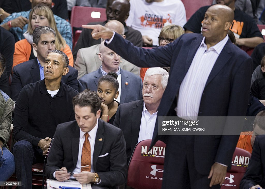 US President Barack Obama watches as his brotherinlaw Craig Robinson coaches during a basketball game at the University of Maryland's Comcast Center...