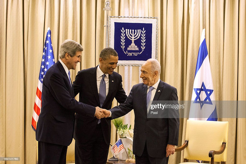 U.S. President Barack Obama (C) watches as U.S. Secretary of State John Kerry shakes hands with Israeli President Shimon Peres (R) during a welcome ceremony at the President's residence on March 20, 2013 in Jerusalem, Israel. This will be Obama's first visit as president to the region, and his itinerary will include meetings with the Palestinian and Israeli leaders as well as a visit to the Church of the Nativity in Bethlehem.