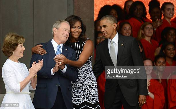 President Barack Obama watches first lady Michelle Obama embracing former president George Bush accompanied by his wife former first lady Laura Bush...