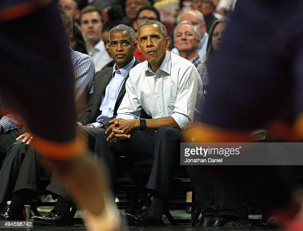President Barack Obama watches from courtside during the season opening game between the Chicago Bulls and the Cleveland Cavaliers at the United...