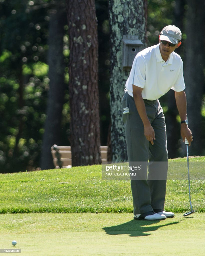 US President Barack Obama watches his putt on the first green as he plays golf at the Farm Neck Golf Club at Martha's Vineyard, Massachusetts, on August 9, 2014, on the first day of the president's yearly summer vacation on the island. AFP PHOTO/Nicholas KAMM